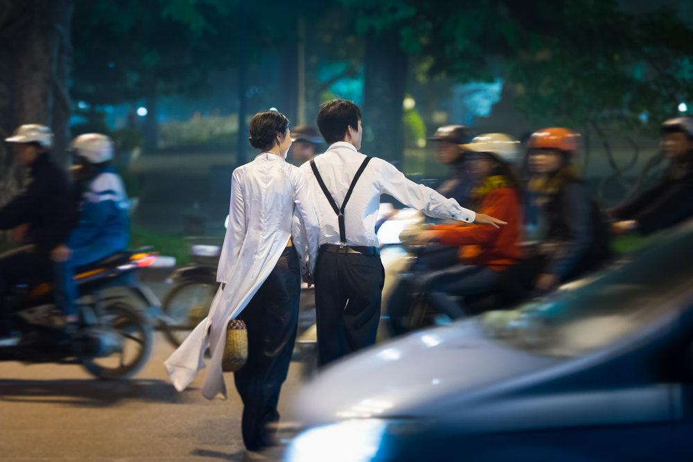 Vacanze in Vietnam coppia attraversa la strada nel traffico